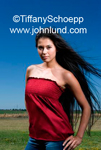 Portrait of a beautiful young Hispanic woman standing proud outdoors with her long black hair blowing in the wind. She is wearing a sexy red blouse and blue jeans.